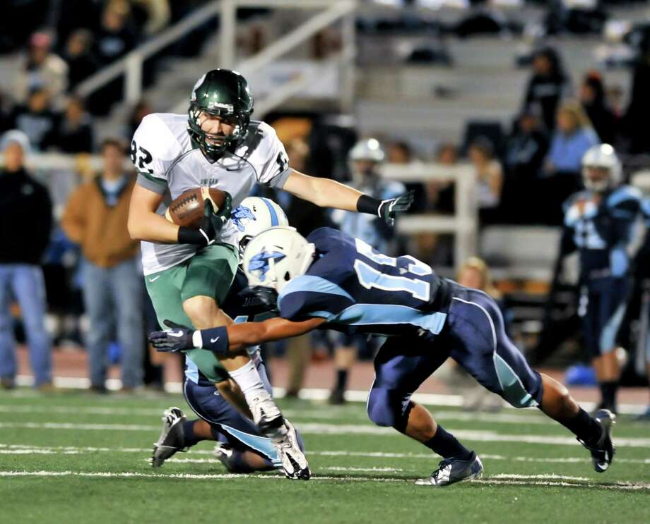 Reagan receiver John Grubb is tackled by Johnson's Fernando Cruz (15) after making a midfield catch. Photo: Express-News