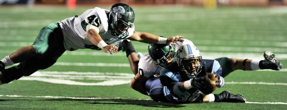 Johnson's Xavier McElhannon stretches for some extra yardage while being tackled by Reagan's Gus Pena (45) and Garrett Strauss. Photo: Express-News