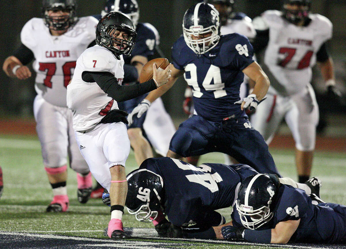 New Braunfels Canyon's Philip Shelton tries to shake the tackle of Smithson Valley's Tristan Wilson and George Schwanenberg during first half action Friday Oct. 26, 2012 at Ranger Stadium in Spring Branch, Tx. Shelton was sacked on the play.