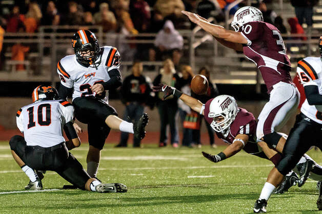 Floresville's Kyle Bippert (lower right) blocks an extra point attempt by Medina Valley's Jonathan Groff during the first quarter of their game at Eschenberg Field in Flooresville on Oct. 26, 2012.  Medina Valley beat the Tigers 27-13.  MARVIN PFEIFFER/ mpfeiffer@express-news.net Photo: MARVIN PFEIFFER, Express-News / Express-News 2012