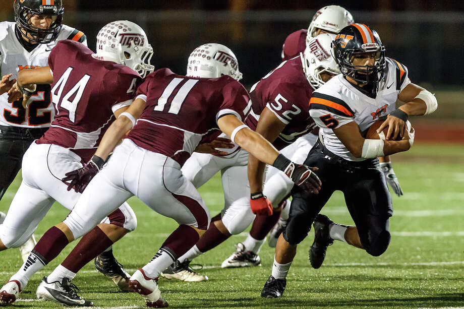 Medina Valley's Ben Mata (right) runs past Floresville's Alex Douglas (from left) Kyle Bippert and Nick Wilkerson during the third quarter of  their game at Eschenberg Field in Flooresville on Oct. 26, 2012.  Mata rushed for 194 yards on 33 carries scoring a toudhdown and a two-point conversion to help the Panthers beat Floresville 27-13.  MARVIN PFEIFFER/ mpfeiffer@express-news.net Photo: MARVIN PFEIFFER, Express-News / Express-News 2012
