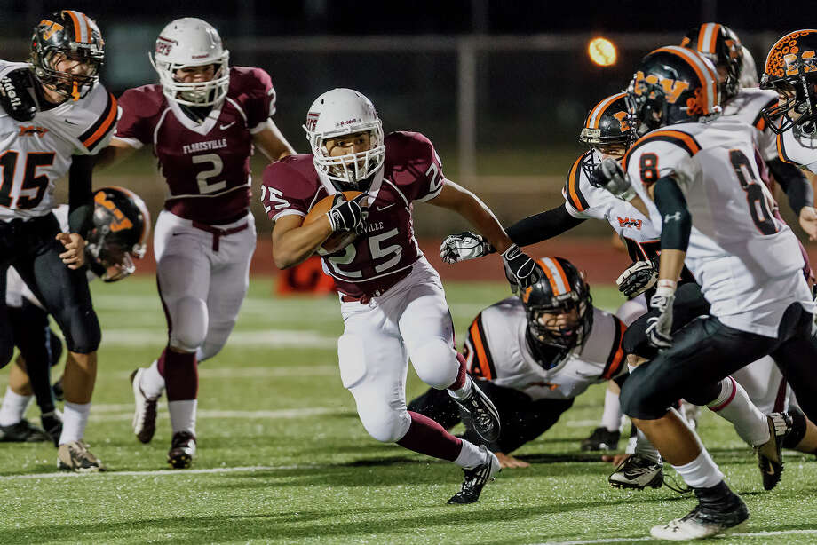 Floresville's Hector Villegas (center) looks for daylight during their game with Medina Valley at Eschenberg Field in Flooresville on Oct. 26, 2012.  Medina Valley beat the Tigers 27-13.  MARVIN PFEIFFER/ mpfeiffer@express-news.net Photo: MARVIN PFEIFFER, Express-News / Express-News 2012