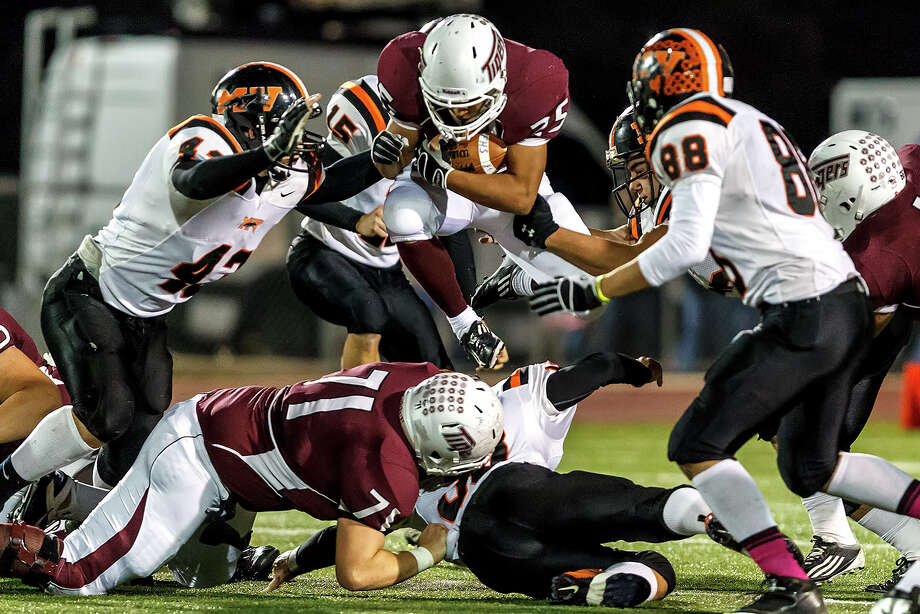 Floresville's Hector Villegas (center) picks up a first down during the second quarter of their game with Medina Valley at Eschenberg Field in Flooresville on Oct. 26, 2012. Villegas ran for 167 yards and a touchdown on 29 carries but Medina Valley beat the Tigers 27-13 .  MARVIN PFEIFFER/ mpfeiffer@express-news.net Photo: MARVIN PFEIFFER, Express-News / Express-News 2012