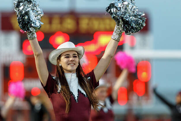 Floresville Tigerette colonel Corinne Morkovsky raises her pom poms as the school song is sung prior to their game with Medina Valley at Eschenberg Field in Flooresville on Oct. 26, 2012.  MARVIN PFEIFFER/ mpfeiffer@express-news.net Photo: MARVIN PFEIFFER, Express-News / Express-News 2012