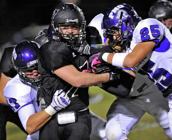 Pirate #7, Justin Moore, center, tries to avoid two Indian defensivemen,  #47, Chase Woods, left, and #25, Corbin Coy, as he heads up field for the gain.  The Vidor High School Pirates hosted the Port Neches-Groves Indians football team Friday night October 26, 2012 at Pirate Stadium.  Dave Ryan/The Enterprise Photo: Dave Ryan