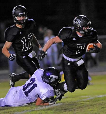 Pirate  #7, Justin Moore, center, blows through an opening in the PN-G defense made by his teammates, but Indian #31, Robert Dawson, left, brings him down by his feet.   The Vidor High School Pirates hosted the Port Neches-Groves Indians football team Friday night October 26, 2012 at Pirate Stadium.  Dave Ryan/The Enterprise Photo: Dave Ryan