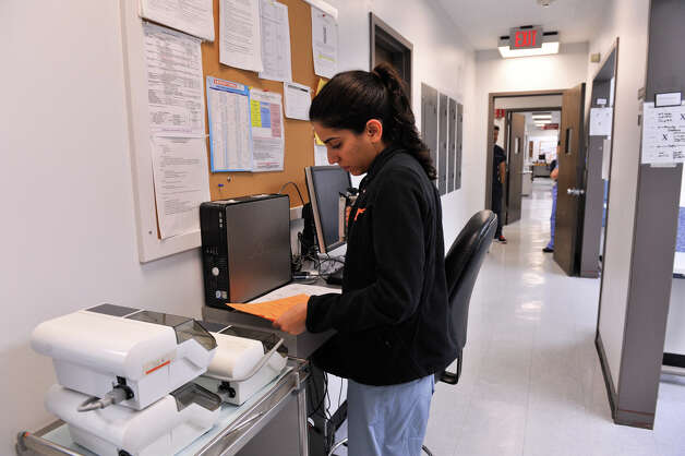 Sanam Safahieh, a fourth year dental student at the University of Texas Health Science Center at San Antonio, looks over paperwork in a hallway on Oct. 22, 2012. Photo: Robin Jerstad, For The Express-News