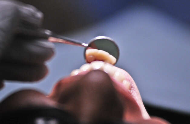 Winston Faltine, a fourth year dental student, examines the teeth of patient Patricia Torres Alvarez at the University of Texas Health Science Center at San Antonio on Oct. 22, 2012. Photo: Robin Jerstad, For The Express-News