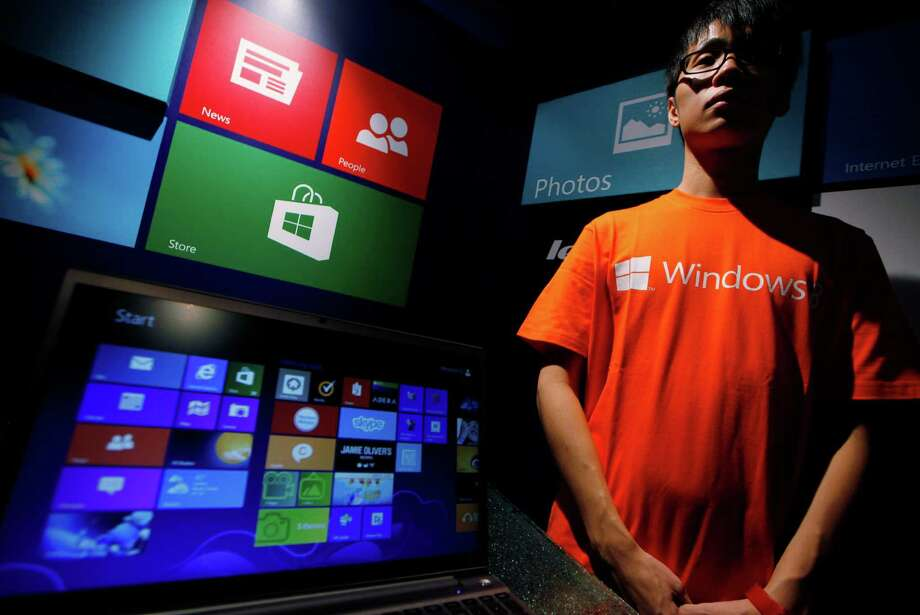 An attendant stands ready to help during a Windows 8 launching ceremony Friday in Hong Kong. Microsoft was introducing a radical redesign of its world-dominating Windows system. Photo: Kin Cheung, STF / AP