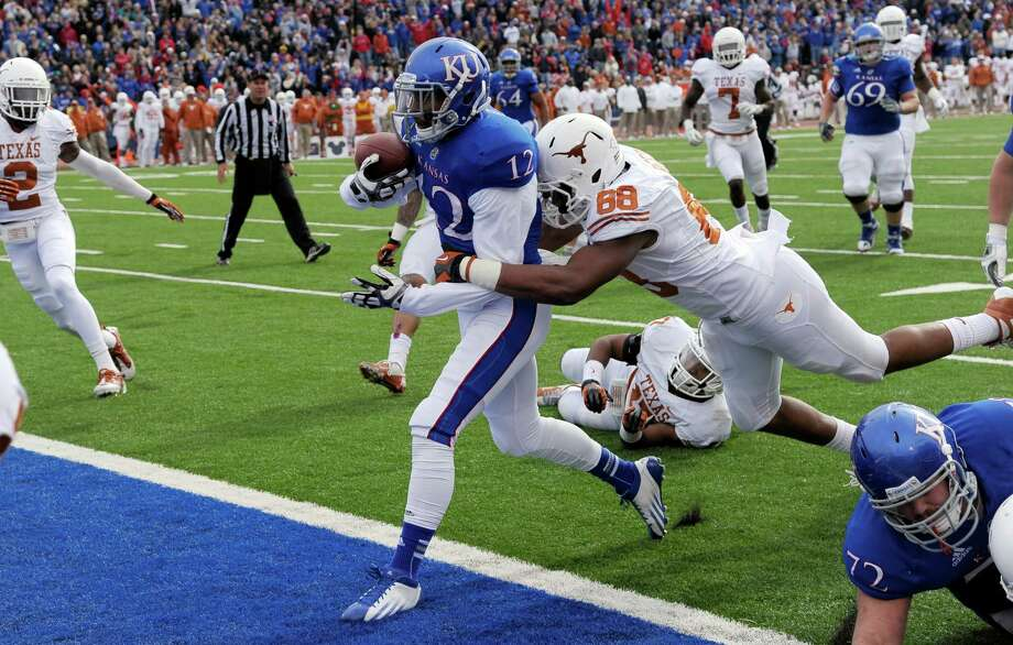 Texas 21, Kansas 17Kansas wide receiver Christian Matthews (12) drags Texas defensive end Cedric Reed (88) into the end zone to score a touchdown during the first half of an NCAA college football game in Lawrence, Kan., Saturday, Oct. 27, 2012. (AP Photo/Reed Hoffmann) Photo: Reed Hoffmann, Associated Press / FR48783 AP