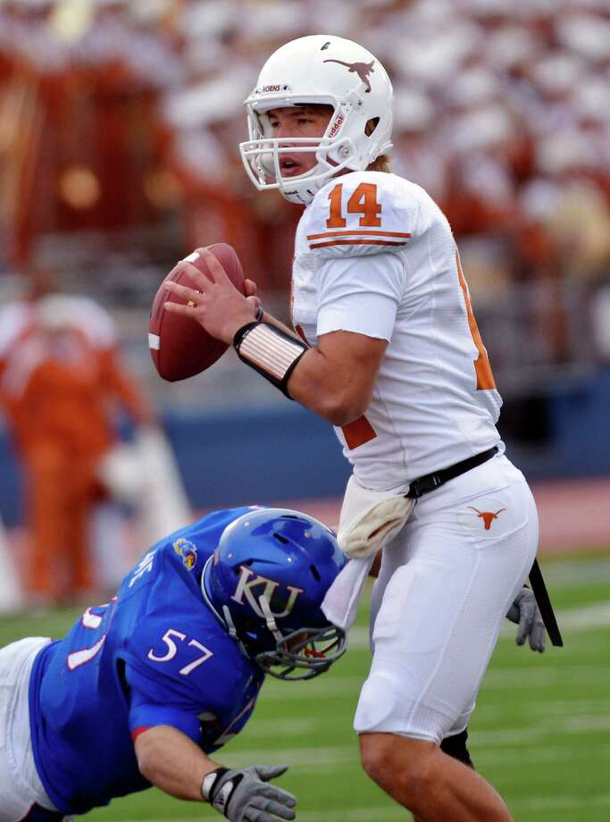 Texas quarterback David Ash (14) is sacked by Kansas linebacker Jake Love (57) during the first half of an NCAA college football game in Lawrence, Kan., Saturday, Oct. 27, 2012. (AP Photo/Reed Hoffmann) Photo: Reed Hoffmann, Associated Press / FR48783 AP