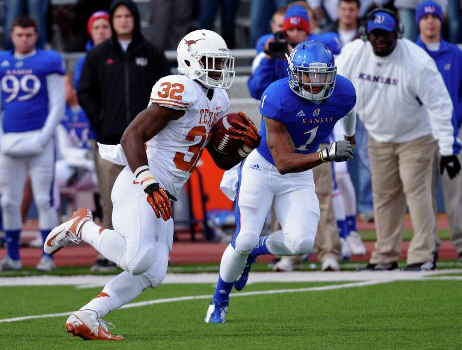 Texas running back Johnathan Gray (32) runs past Kansas safety Lubbock Smith (1) during the first half of an NCAA college football game in Lawrence, Kan., Saturday, Oct. 27, 2012. (AP Photo/Reed Hoffmann) Photo: Reed Hoffmann, Associated Press / FR48783 AP