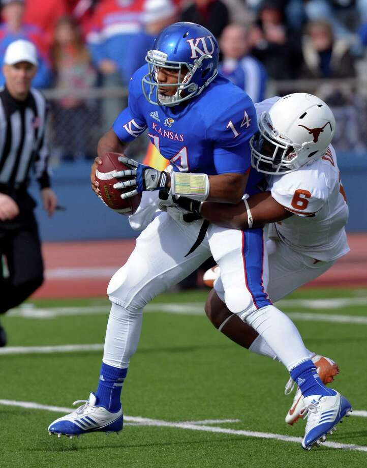 Texas cornerback Quandre Diggs, right, sacks Kansas quarterback Michael Cummings (14) during the first half of an NCAA college football game in Lawrence, Kan., Saturday, Oct. 27, 2012. (AP Photo/Reed Hoffmann) Photo: Reed Hoffmann, Associated Press / FR48783 AP