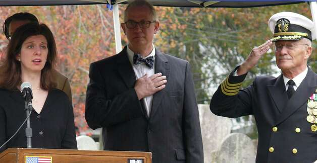 Colleen Cooney sings the national anthem, as the Rev. David Spollett and retired naval Capt. Roger Crossland salute, during Saturday ceremony marking the rededication of the headstone of Capt. Samuel Smedley in the Old Burying Grounds. Photo: Genevieve Reilly