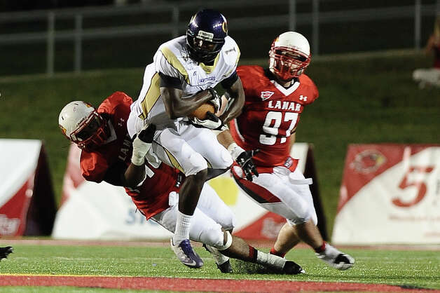 Prairie View wide receiver Deandre Coper tackled by linebacker Jermaine Longino at Provost Umphrey Stadium on Saturday, September 8, 2012. Photo taken: Randy Edwards/The Enterprise