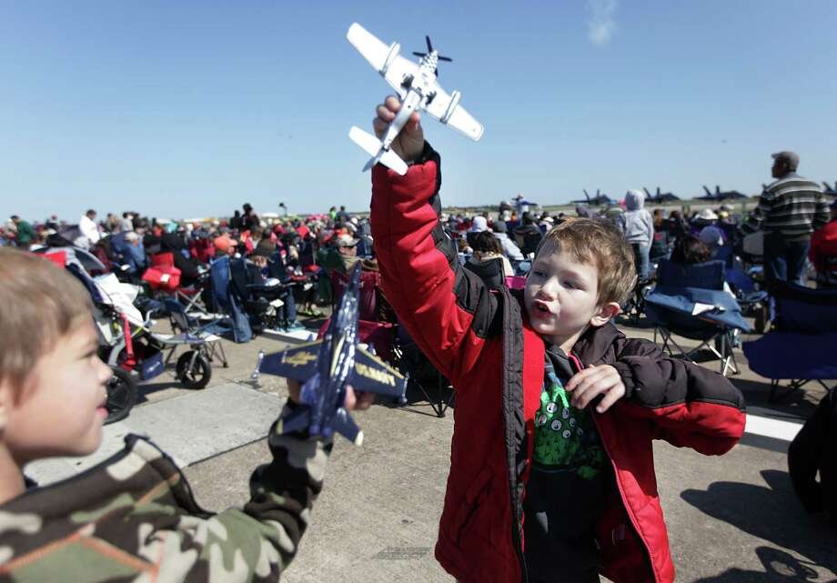 (Left to right)  Nathaniel Kenkide, 7, and friend Devin Smith, 7, play with their plastic airplanes during the 28th Annual Wings Over Houston Airshow at  Ellington Field on Saturday, Oct. 27, 2012, in Houston. Photo: Mayra Beltran, Houston Chronicle / Houston Chronicle