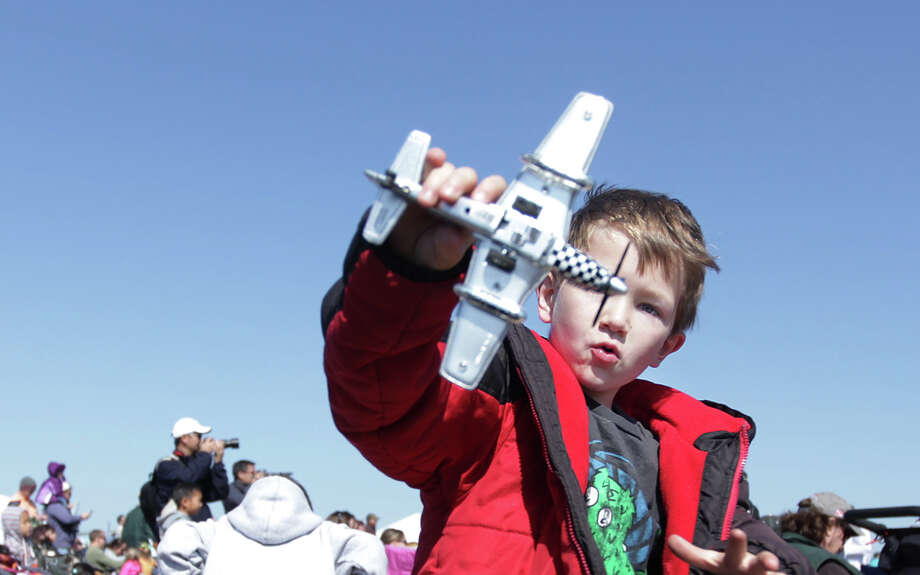 Devin Smith, 7, plays with his plastic airplane model during the 28th Annual Wings Over Houston Airshow at  Ellington Field on Saturday, Oct. 27, 2012, in Houston. Photo: Mayra Beltran, Houston Chronicle / Houston Chronicle