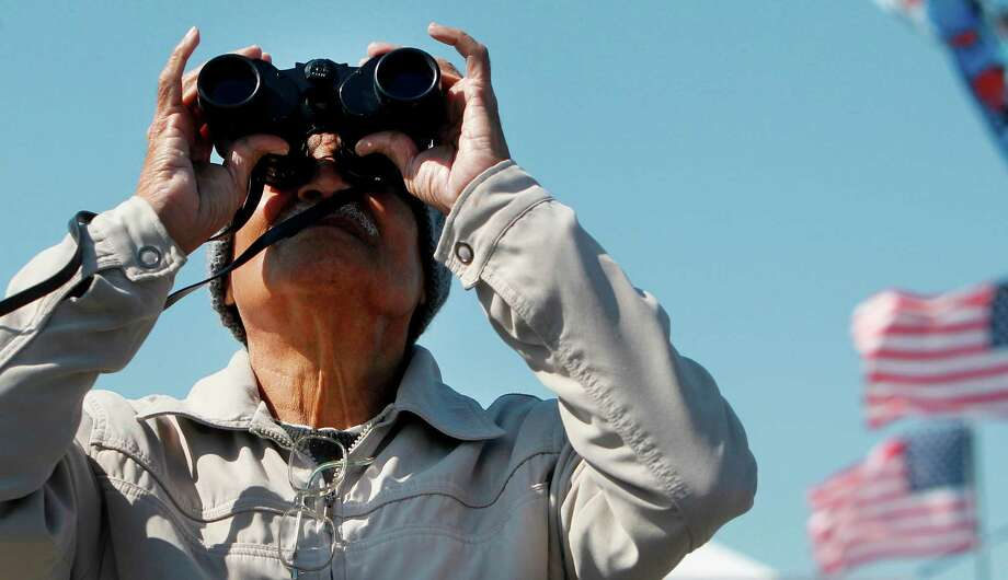 Vijay Hardikar gets a closer look of the aircraft with his binoculars during the 28th Annual Wings Over Houston Airshow at  Ellington Field on Saturday, Oct. 27, 2012, in Houston. Photo: Mayra Beltran, Houston Chronicle / Houston Chronicle
