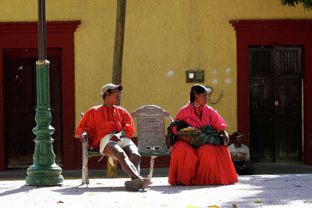 "Tarahumaras hang out at the town's plaza in Batopilas, Mexico, Sunday, Oct. 7, 2012. The town, at the bottom of Batopilas Canyon in Chihuahua, held the annual public address by Mayor Leonel Hernandez. With it came free food and music until late Saturday. The once-popular tourist destination remains largely untouched by modernity. With the drug war crisis affecting the area and the rest of the country, tourism has come to a standstill. ""It's a hugh crisis for Batopilas. Tourism supports a lot of people. It's very severe and the government can do very little,"" said city administrator Rafael Gastelum. Photo: Jerry Lara, San Antonio Express-News / San Antonio Express-News"