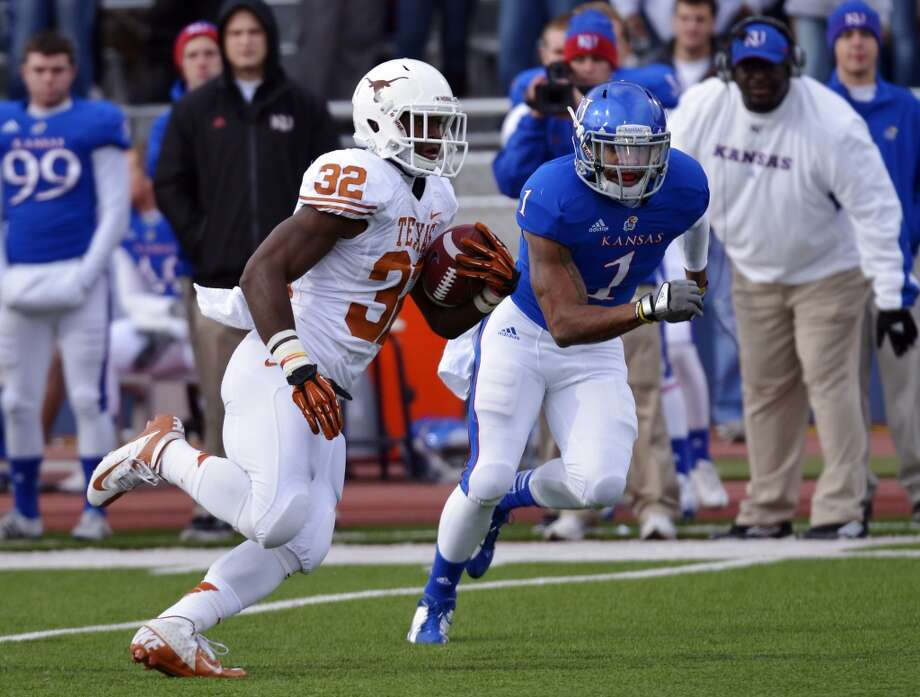 Texas running back Johnathan Gray (32) runs past Kansas safety Lubbock Smith (1) during the first half of an NCAA college football game in Lawrence, Kan., Saturday, Oct. 27, 2012. (AP Photo/Reed Hoffmann) (Associated Press)