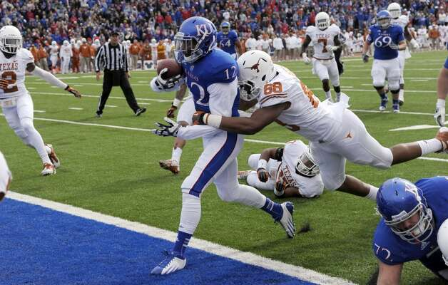 Kansas wide receiver Christian Matthews (12) drags Texas defensive end Cedric Reed (88) into the end zone to score a touchdown during the first half of an NCAA college football game in Lawrence, Kan., Saturday, Oct. 27, 2012. (AP Photo/Reed Hoffmann) (Associated Press)