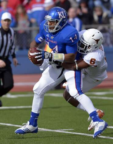 Texas cornerback Quandre Diggs, right, sacks Kansas quarterback Michael Cummings (14) during the first half of an NCAA college football game in Lawrence, Kan., Saturday, Oct. 27, 2012. (AP Photo/Reed Hoffmann) (Associated Press)