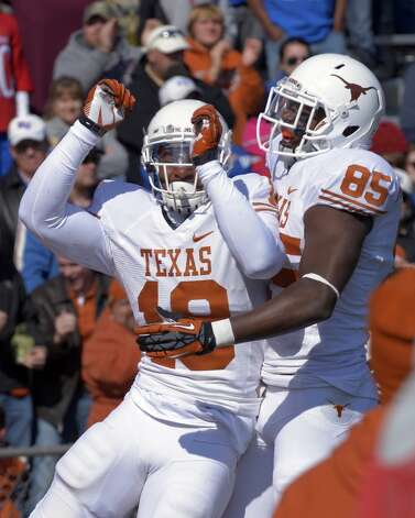 Texas tight end D.J. Grant (18) celebrates with teammate M.J. McFarland (85) after scoring the go-ahead touchdown with less than a minute to play against the Kansas during the second half of a NCAA college football game in Lawrence, Kan., Saturday, Oct. 27, 2012. Texas won 21-17. (AP Photo/Reed Hoffmann) (Associated Press)