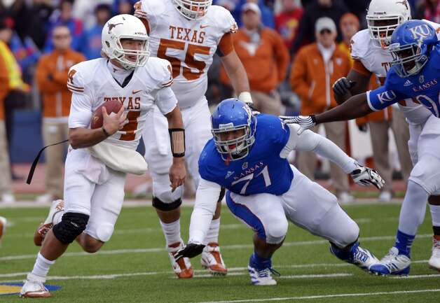 Texas quarterback David Ash (14) runs past Kansas defensive lineman John Williams (71)  during the first half of an NCAA college football game in Lawrence, Kan., Saturday, Oct. 27, 2012. (AP Photo/Reed Hoffmann) (Associated Press)