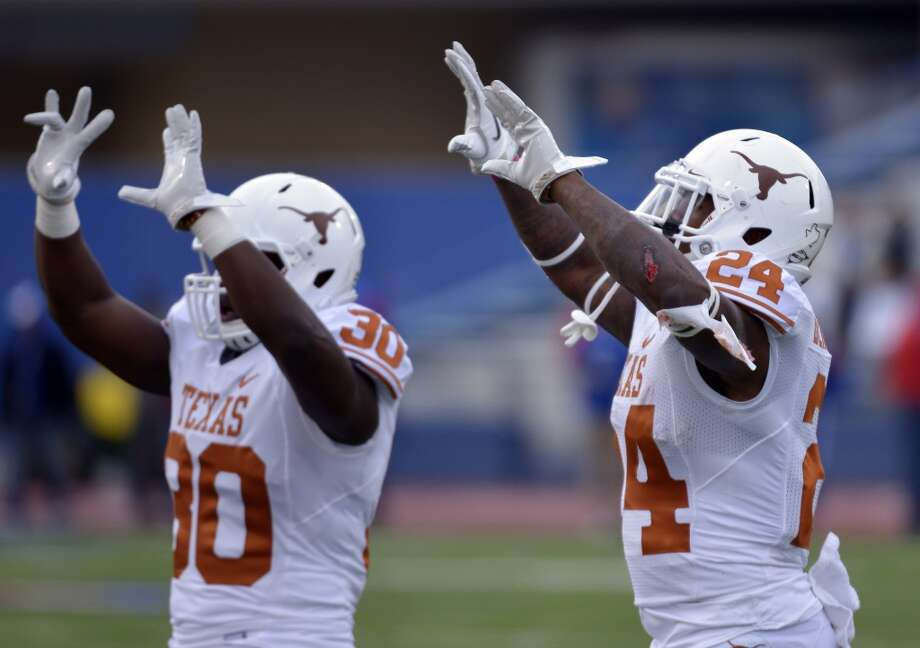 Texas running back Joe Bergeron, right, celebrates his touchdown against the Kansas with teammate Ryan Roberson (30) during the first half of an NCAA college football game in Lawrence, Kan., Saturday, Oct. 27, 2012. (AP Photo/Reed Hoffmann) (Associated Press)