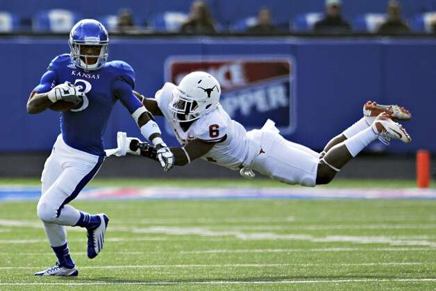 Kansas running back Tony Pierson evades Texas safety Quandre Diggs during the second half of NCAA football game, Saturday, Oct. 27,2 012, in Lawrence, Kansas. (AP Photo/The Daily Texan, Lawrence Peart) (Associated Press)