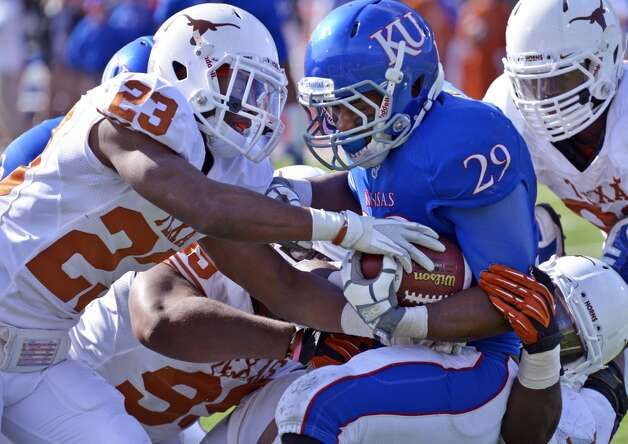 Texas cornerback Carrington Byndom (23) tries to pull the ball from Kansas running back James Sims (29) during the second half of an NCAA college football game in Lawrence, Kan., Saturday, Oct. 27, 2012. (AP Photo/Reed Hoffmann) (Associated Press)