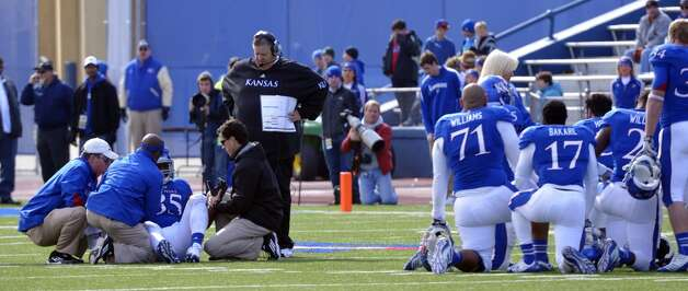 Kansas head coach Charlie Weis, center, and his team look on as Kansas defensive end Toben Opurum (35) was tended to during the second half of an NCAA college football game against Texas in Lawrence, Kan., Saturday, Oct. 27, 2012. (AP Photo/Reed Hoffmann) (Associated Press)
