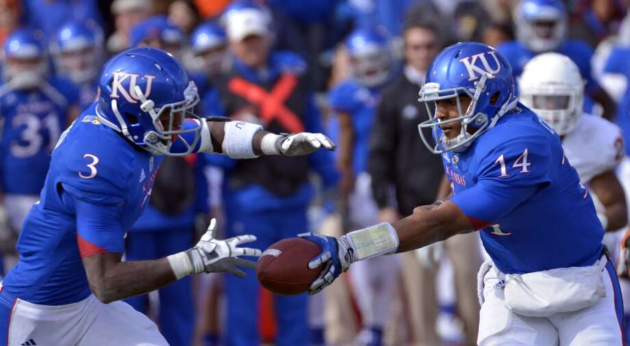 DKansas Jayhawks quarterback Michael Cummings (14) hands off to running back Tony Pierson (3) during the second half of an NCAA college football game against Texas in Lawrence, Kan., Saturday, Oct. 27, 2012. (AP Photo/Reed Hoffmann) (Associated Press)