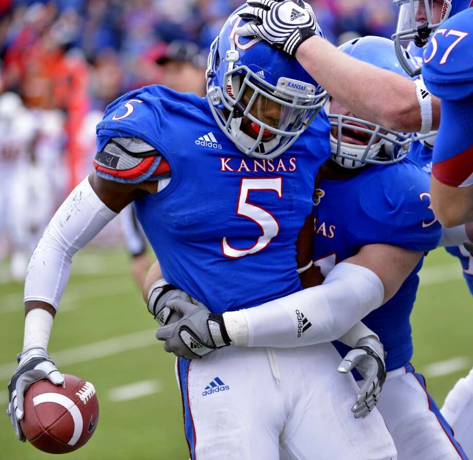 Kansas cornerback Greg Brown (5) is congratulated after making an interception late in the first half of an NCAA college football game against Texas in Lawrence, Kan., Saturday, Oct. 27, 2012. (AP Photo/Reed Hoffmann) (Associated Press)