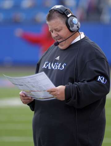 Kansas head coach Charlie Weis looks at his charts during the first half of an NCAA college football game against Texas in Lawrence, Kan., Saturday, Oct. 27, 2012. (AP Photo/Reed Hoffmann) (Associated Press)