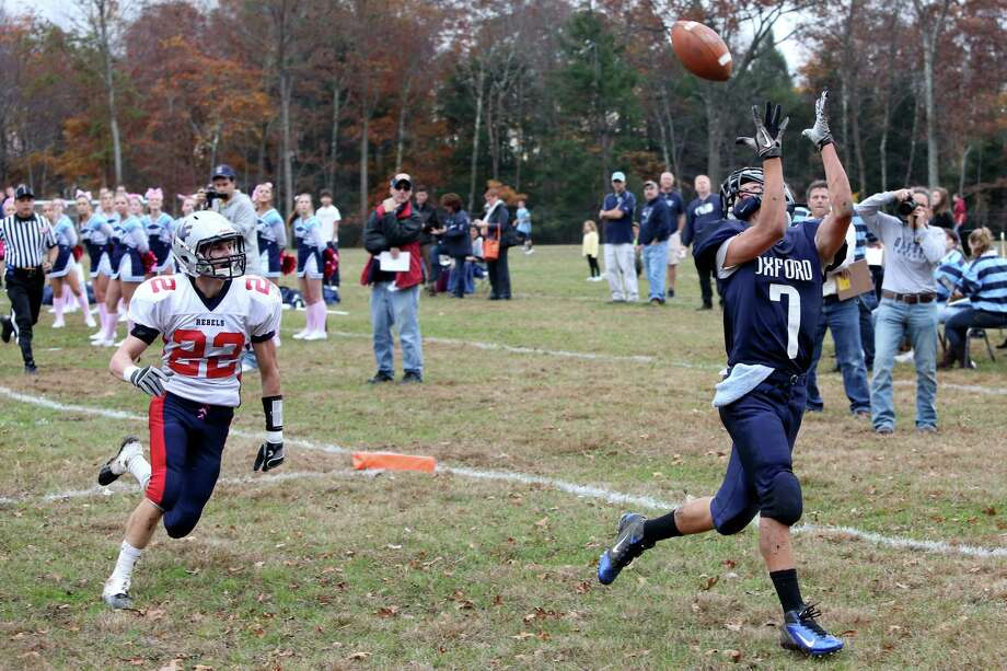Mike Ross Connecticut Post freelance - Oxford High School's # 7 Chris Vankamerik eyes a touchdown pass as New Fairfield's # 22 Collin Cioffi gives chase during first half action on Saturday Photo: Mike Ross