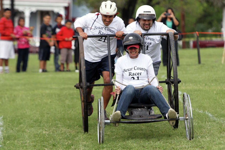 Patti Hawley of the Bexar County Racers is pushed along by employees of the Bexar County Juvenile Detention Center on a cart modified from an old donkey cart during the 8th Annual Dignowity Hill Push Cart Derby at Dignowity Hill Park, Saturday, October 27, 2012. Photo: Jennifer Whitney, For The Express-News / © Jennifer Whitney