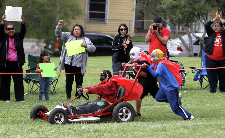 The Bowdowin Elementary Little Luchares race toward the finish line of the Dignowity Hill Push Cart Derby. Several hundred people also enjoyed a three-piece jazz band and free samples of Alamo Golden Ale. Photo: Jennifer Whitney, For The Express-News / © Jennifer Whitney