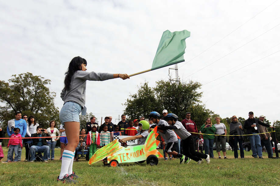 Flagger Xelina Flores-Chasnoff waves the flag to start a heat during the 8th Annual Dignowity Hill Pushcart Derby at Push Cart Hill Park, Saturday, October 27, 2012. Photo: Jennifer Whitney, For The Express-News / © Jennifer Whitney