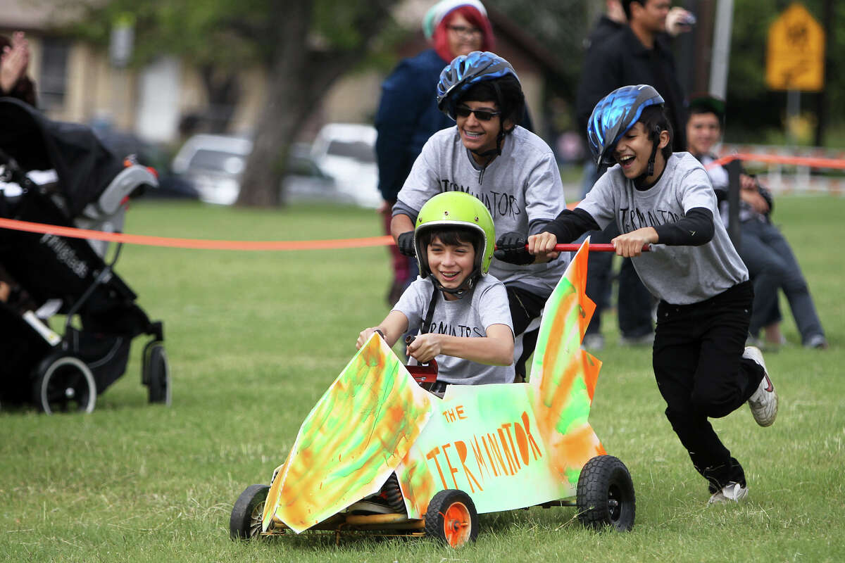 The Terminator, driven by Joaquin Ortiz, 11, and pushed by Michael Bernal, 13, and his brother, Marcus Bernal, 11, races to the finish line during the 8th Annual Dignowity Hill Push Cart Derby at Dignowity Hill Park, Saturday, October 27, 2012.