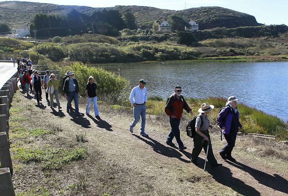 Visitors walk past Rodeo Lagoon on a hike led by park founders at the Marin Headlands. Photo: Paul Chinn, The Chronicle