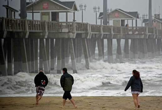 Beachgoers walk in the wind and rain as waves generated by Hurricane Sandy crash into Jeanette's Pier in Nags Head, N.C., Saturday, Oct. 27, 2012 as the storm churns up the east coast. Hurricane Sandy, upgraded again Saturday just hours after forecasters said it had weakened to a tropical storm, was barreling north from the Caribbean and was expected to make landfall early Tuesday near the Delaware coast, then hit two winter weather systems as it moves inland, creating a hybrid monster storm. Photo: Gerry Broome