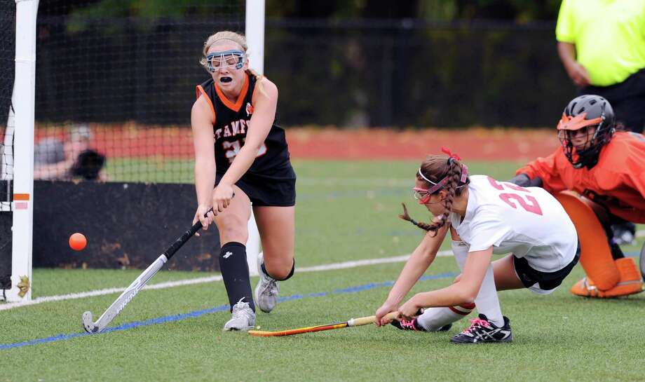 At right, Elizabeth Stillman # 22 of Greenwich shoots as Stamford's Ciara Killian # 23 attempts to block the shot during the FCIAC field hockey tournament match between Stamford High School and Greenwich High School at Greenwich, Saturday afternoon, Oct. 27, 2012. At right is Lesly Sanchez the  Stamford goalie. Stillman did not score on the shot. Photo: Bob Luckey / Greenwich Time