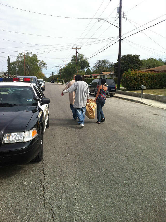 A woman and two men carry the carcass of a dog down J Street after it was fatally shot by a San Antonio police officer. The dog reportedly bit a man who tried to intervene after he saw the canine tear the pants off of its female owner; the woman, pictured, told officers the dog was just being playful. Photo by Eva Ruth Moravec/San Antonio Express-News