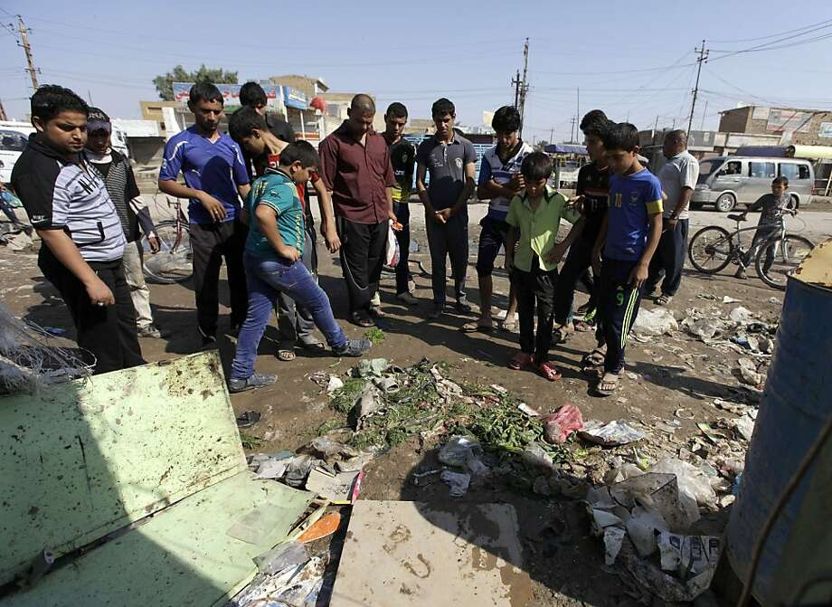 Iraqis gather at the scene of a bomb attack near a playground in Baghdad that killed eight people. Photo: Khalid Mohammed, Associated Press