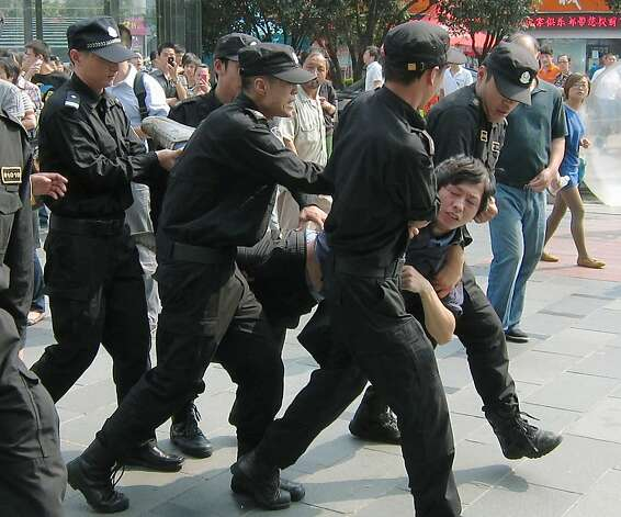 Chinese police officers carry a demonstrator away while people protest the proposed expansion of a petrochemical factory that they say would spew pollution and damage public health in Ningbo, Zhejiang province, China on Saturday, Oct. 27, 2012. Pollution has become a major source of unrest in China, as members of the rising middle class become more outspoken against environmentally risky projects in their backyards. Photo: Associated Press
