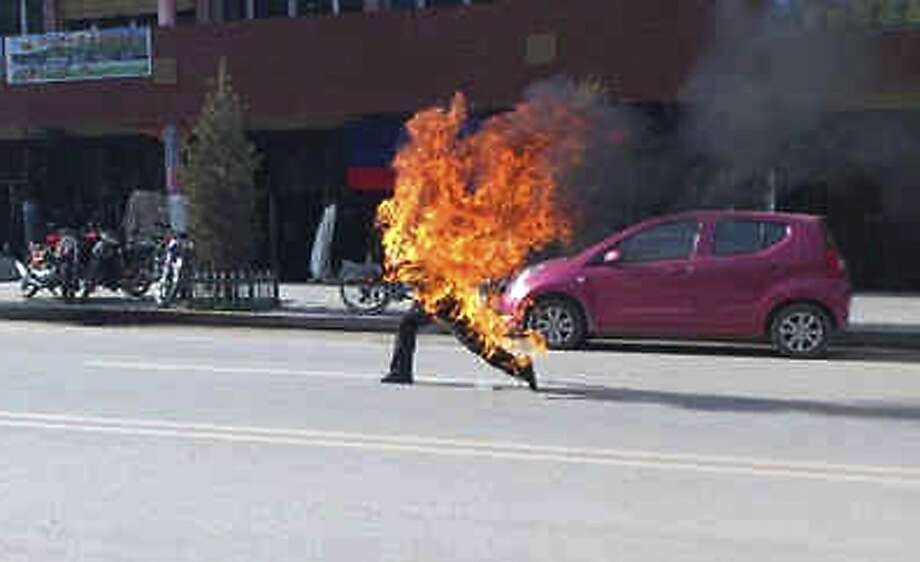 In this photo taken Tuesday, Oct 23, 2012 and released by London-based rights group Freetibet.org, Dorje Rinchen, a farmer in his late 50s, runs after setting himself on fire on the main street in Xiahe in northwestern China's Gansu province. This was the second self-immolation death in two days near the Labrang monastery in Xiahe. The monastery is one of the most important outside of Tibet and was the site of numerous protests by monks following deadly ethnic riots in Tibet in 2008 that were the most sustained Tibetan uprising against Chinese rule in decades. Photo: Associated Press