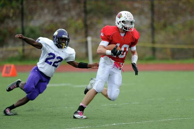 Greenwich's Taylor Olmstead carries the ball as Westhill's Tyreece Mitchell follows closely behind during Saturday's football game at Westhill High School on October 27, 2012. Photo: Lindsay Niegelberg