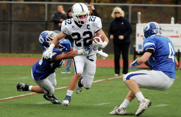 Staples' Joey Zelkowitz carries as Darien's Peter Gesualdi, left, and Jackson Whiting close in as Darien High School hosts Staples in a football game in Darien, Conn., Oct. 27, 2012. Photo: Keelin Daly