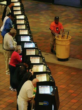 Early voters fill out their ballots as they cast their vote in the presidential election on the first day of early voting Saturday in Miami. Early voting in one of the important swing states — Florida — is held for eight straight 12-hour days, leading up to Nov. 6. Photo: Joe Raedle, Getty Images / 2012 Getty Images